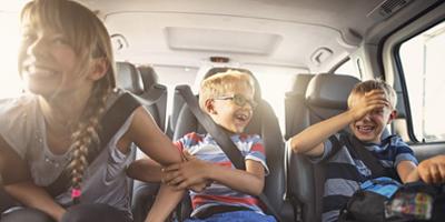 Een meisje en twee jongetjes hebben plezier op de achterbank van een auto. Bij UMC Zorgverzekering zijn kinderen gratis meeverzekerd.